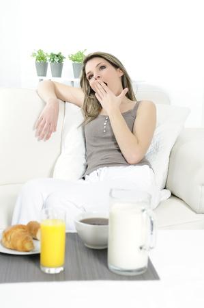 sprawled: mujer en su sof� antes de despertar su desayuno Foto de archivo