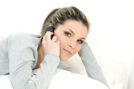 inddor: young beautiful woman on telephone in his sofa