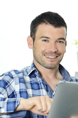 attractive relaxed and positive man is surfing on his tablet Stock Photo - 9530066