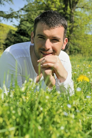 An attractive and cheerful man lying in the park Stock Photo - 9530114