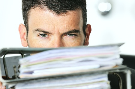 busy man hiding behind a stack of files photo