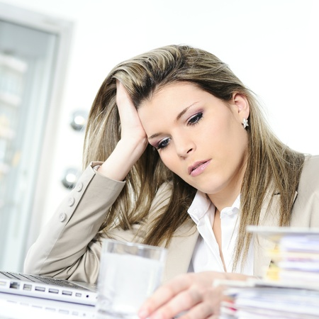 young woman stressed at work, taking an aspirin cahet