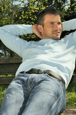 ser humano: hombre atractivo es relajante en un banco en un entorno natural Foto de archivo
