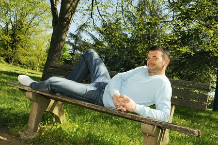 attractive man is relaxing on a bench in a natural environement Stock Photo - 9979338
