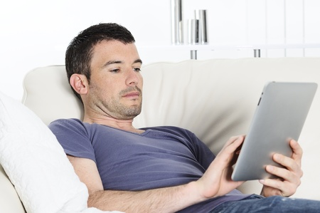 attractive relaxed and positive man is surfing on his tablet Stock Photo