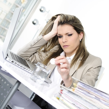 young woman stressed at work, taking an aspirin cahet photo