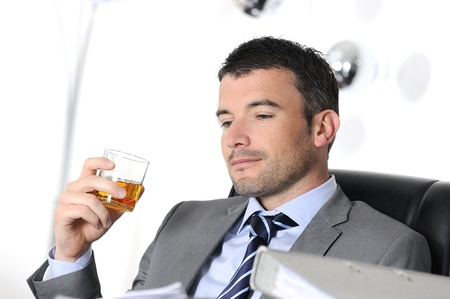 addiction drinking: business man is drinking alchool at the office Stock Photo