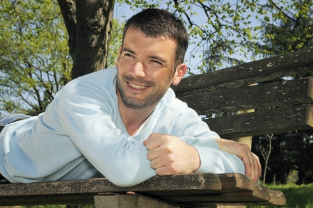 early 30s: attractive man is relaxing on a bench in a natural environement