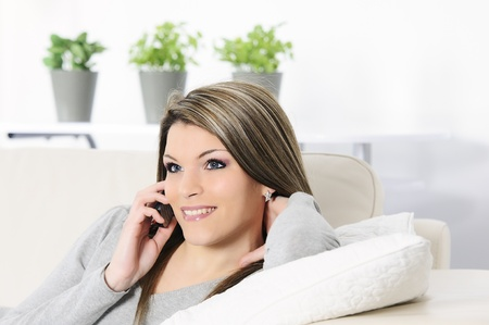 inddor: attractive and cheerful woman on telephone in his sofa