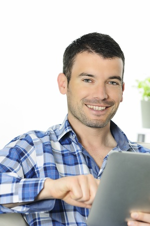 attractive relaxed and positive man is surfing on his tablet photo