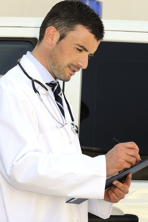 doctor is writing a report behind an ambulance Stock Photo - 12148945