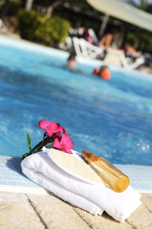 massage oil, shellfish and white towel beside a pool photo