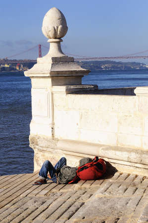 view of Tagus in Lisbon and a poor and homeless black man photo