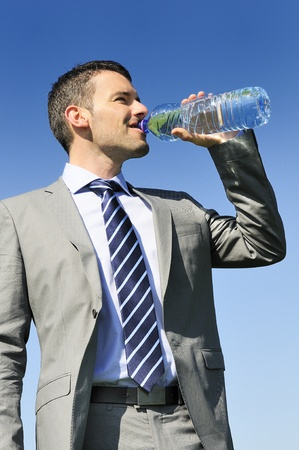 businessman in suit is drinking fresh water in a bottle Stock Photo