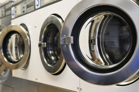 industrial machine: A row of industrial washing machines in a public laundromat  Stock Photo