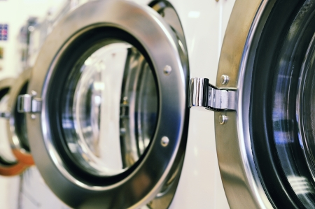 laundromat: A row of industrial washing machines in a public laundromat  Stock Photo