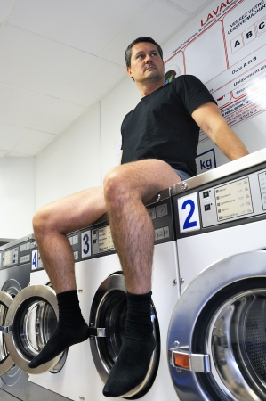 laundromat: man is using washing machines in a public laundromat  Stock Photo