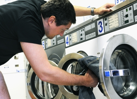 man laundry: man is using washing machines in a public laundromat  Stock Photo