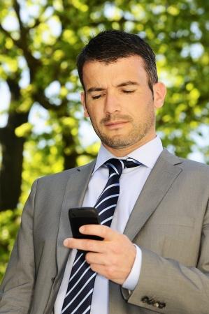 Geschäftsmann ist mit einer Kommunikation mit seinem Mobiltelefon Standard-Bild - 14153081