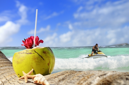Coconut with drinking straw on a palm tree at the sea and jetski time photo