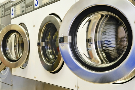A row of industrial washing machines in a public laundry photo