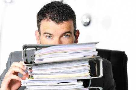 voluminous: busy man hiding behind a stack of files