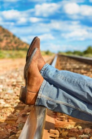 famoso cow-boy stivali e piedi in tutta binari del treno