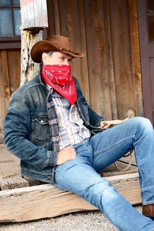 bandana western: OUT WEST - A cowboy takes time to rest and reflect.  Stock Photo