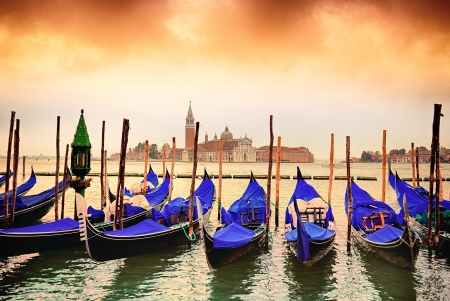 Gondolas moored by Saint Mark square with San Giorgio di Maggiore church in the background - Venice, Venezia, Italy, Europe