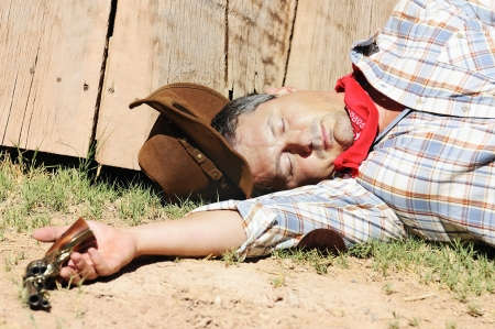 OUT WEST - A cowboy dead with arm in his hand photo