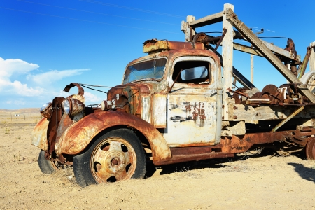 ghost town: vintage truck abandoned and rusting away in the desert, ghost town in the background