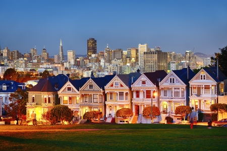 The Painted Ladies of San Francisco, California sit glowing amid the backdrop of a sunset and skyscrapers.  Editorial
