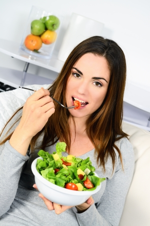 Woman eating salad. Beautiful healthy smiling Caucasian woman enjoying a fresh healthy salad sitting in sofa looking up. High angle view with copy space on modern interior.  photo