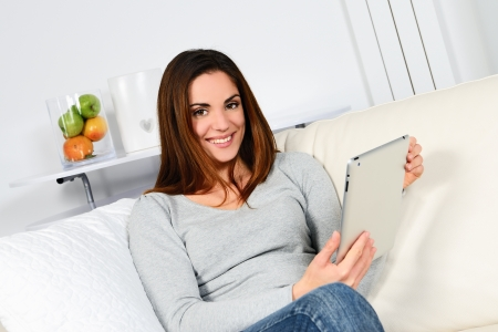 Young woman sitting on sofa with electronic pad Stock Photo - 17823872