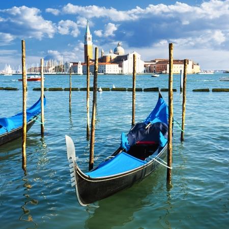 Gondolas moored by Saint Mark square with San Giorgio di Maggiore church in the background - Venice, Venezia, Italy, Europe  photo