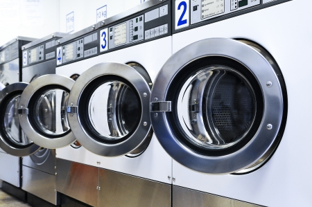 A row of industrial washing machines in a public laundromat  Stock fotó