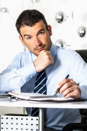 An attractive business man is writing on a paper photo