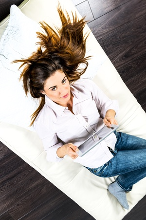 electronic pad: Young woman lying on sofa with electronic pad