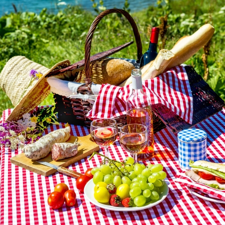 wicker basket: tasted picnic on the grass near a lake