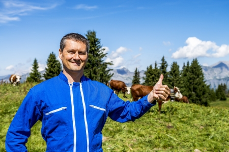 Herdsman standing in front of cows in alpine mountains photo