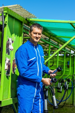 Herdsman standing in front of a machine milking cows Stock Photo - 21707495