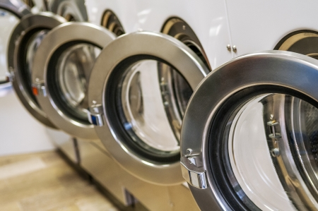 laundry: A row of industrial washing machines in a public laundromat  Stock Photo