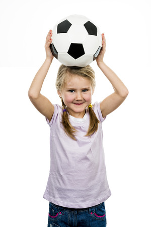 Cute girl playing football, happy child, young female goalkeeper enjoying sport game, holding ball, isolated portrait of a preteen smiling and having fun, kids activities, little footballer  photo