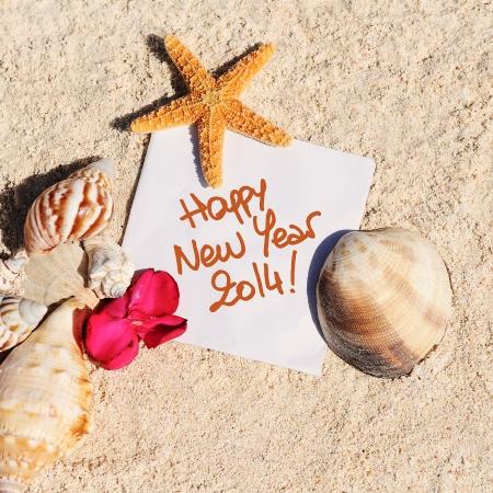 leeres Papier auf weißem Sandstrand mit Seesternen und Muscheln wie Sommerferien Hintergrund Standard-Bild