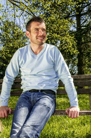attractive man is relaxing on a bench in a natural environement photo
