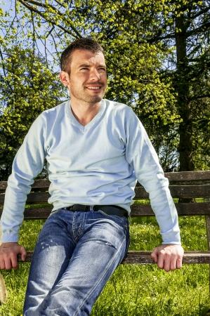 attraktiver Mann sitzt auf einer Bank Entspannung in einer natürlichen environement
