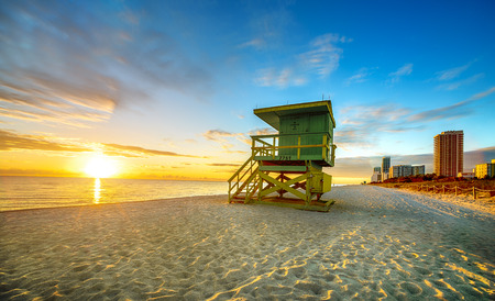 Miami South Beach sunrise with lifeguard tower and coastline with colorful cloud and blue sky
