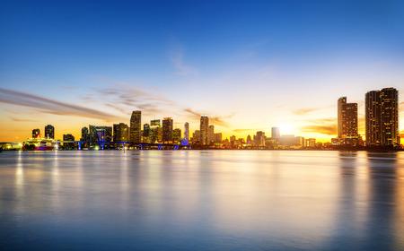 反射と海上都市の高層ビルと夕暮れ時にマイアミ都市スカイラインのパノラマ