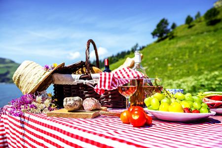 湖の近くの草の上を味わったピクニック 写真素材