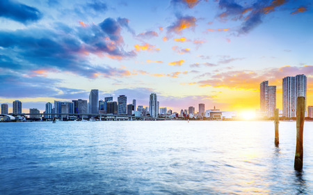 miami: Miami city skyline panorama at dusk with urban skyscrapers over sea with reflection
